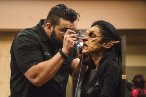 A costume designer puts finishing touches on his werewolf.